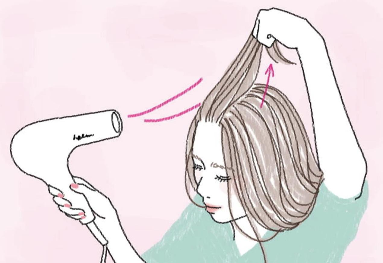 髪を立ち上げてドライヤーを使っている画像